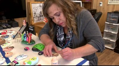 Christine Wiley hand paints rocks with resources on the back for people to learn more about autism.